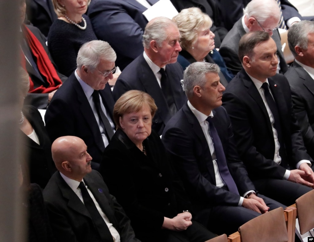Britain's Prince Charles, second from left, back row, and German Chancellor Angela Merkel, second from left, bottom row, are shown seated during a State Funeral for former President George H.W. Bush at the National Cathedral, Dec. 5, 2018.