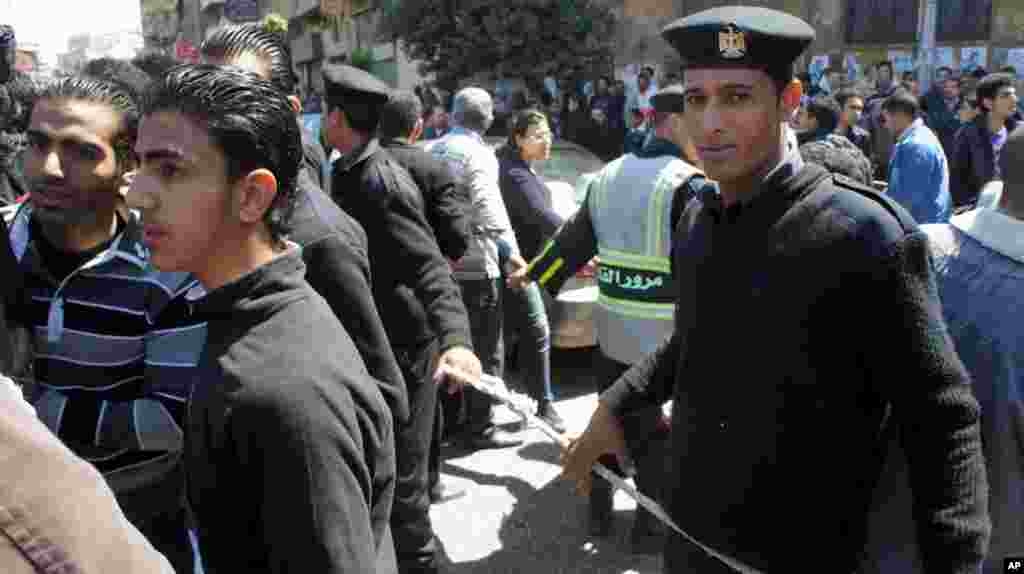 Security helps manage the tens of thousands who came to mourn the Coptic patriarch. (VOA-E. Arrott)