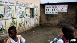 Des enfants marchent devant des panneaux écrits en français, à Kinshasa, en RDC, le 18 janvier 2018.