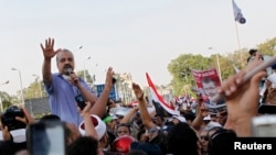 Brotherhood leader Mohamed el-Beltagy (L) shouts slogans with protesters supporting deposed Egypt's President Mohamed Mursi gathering outside the Republican Guard barracks where Mursi is held in Cairo, July 5, 2013.