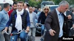 ປະທານາທິບໍດີ ຝຣັ່ງ ທ່ານ Emmanuel Macron ພ້ອມດ້ວຍພັນລະຍາທ່ານນາງ Brigitte Trogneux (ກາງ) ເດີນທາງອອກຈາກບ້ານຂອງພວກເພິ່ນດ້ວຍການຖີບລົດຖີບ ຢູ່ໃນເມືອງ Le Touquet, ປະເທດ ຝຣັ່ງ ໃນມື້ໜຶ່ງກ່ອນການເລືອງຕັ້ງສະພາແຫ່ງຊາດຮອບທຳອິດ. 10 ມິຖຸນາ, 2017.