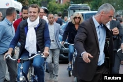 FILE - French President Emmanuel Macron and his wife Brigitte Trogneux (center) leave their home on bicycles in Le Touquet, France, on the eve of the first round of the parliamentary election, June 10, 2017.