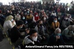Masyarakat sedang mengantre untuk mendapatkan vaksin COVID-19 di Bandara Internasional Juanda, saat kasus melonjak di Sidoarjo, Jawa Timur, 22 Juli 2021. (Foto: Antara/Umarul Faruq via REUTERS)