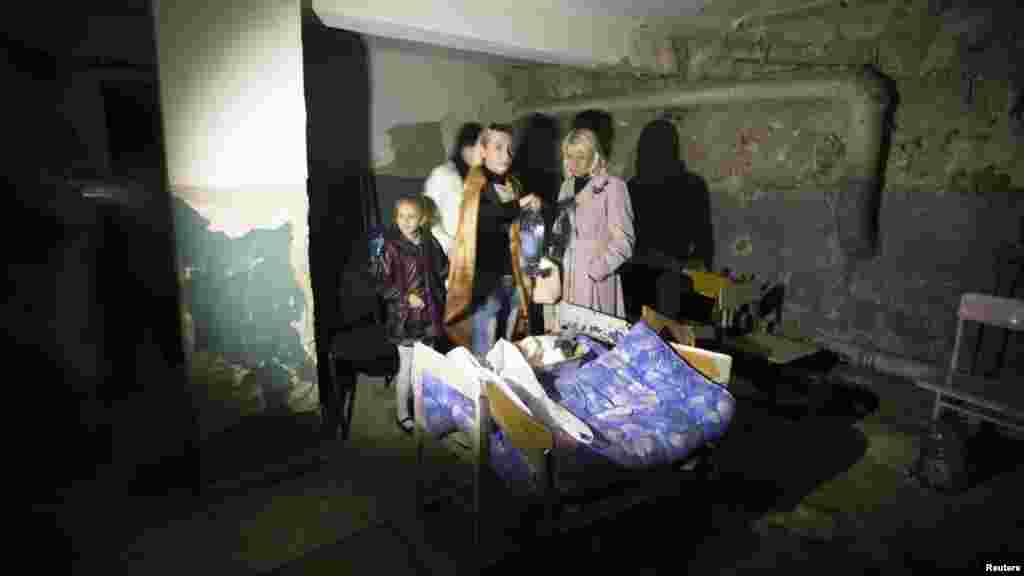 Parents and a pupil hide in a school basement used as a shelter after recent shelling in Donetsk, eastern Ukraine, Oct. 1, 2014.