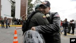 A man embraces a police officer, outside the General Francisco de Paula Santander Police Academy, a day after a car bomb exploded at the site, in Bogota, Colombia, Jan. 18, 2019. Colombia blamed the National Liberation Army, ELN, rebels for the deadly attack.