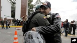 FILE - A man embraces a police officer, outside the General Francisco de Paula Santander Police Academy, a day after a car bomb exploded at the site, in Bogota, Colombia, Jan. 18, 2019.