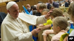 Pope Francis caresses a child during his weekly general audience, in the Pope Paul VI hall, at the Vatican, Aug. 19, 2015.