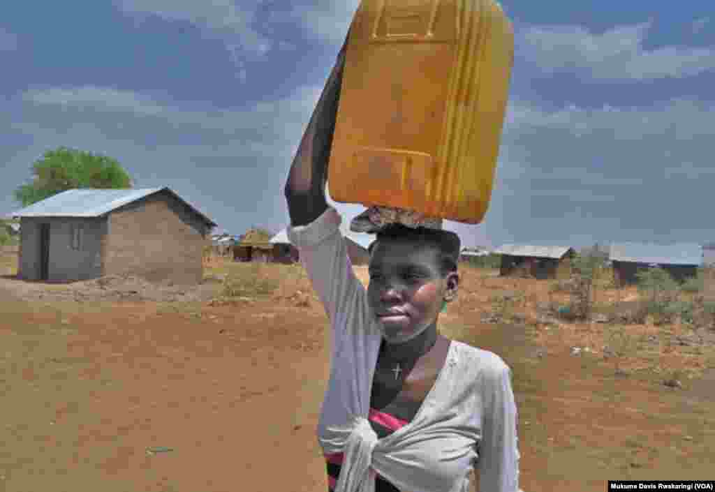 A young woman carries a plastic container to collect water in Gudere, near Juba in South Sudan. Only half the population of South Sudan has access to clean water. (VOA/Mugume Davis Rwakaringi)