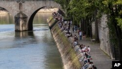 Orang-orang berjalan di sepanjang tepi sungai Seine di Paris, 21 Mei 2020 ketika Perancis secara bertahap melonggarkan karantina wilayah akibat Covid-19. (Foto: AP / Michel Euler)