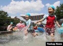 서울에 폭염주의보가 내려진 25일 송파구 성내천 물놀이장을 찾은 어린이들이 더위를 식히고 있다.