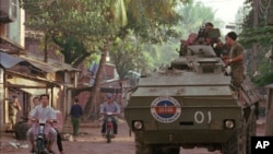 An APC (armored personel carrier) waits on a side street as a few remaining motorists leave an area of Phnom Penh where fighting broke out on Sunday July 6,1997. Fear spread through the city as scattered fighting broke out throughout the capital. APC's an
