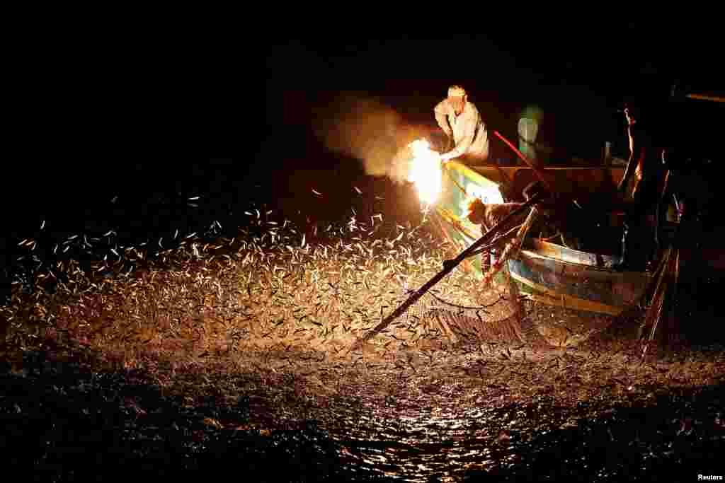 "Fishermen use a fire to attract fish on a traditional ""sulfuric fire fishing"" boat in New Taipei City, Taiwan."
