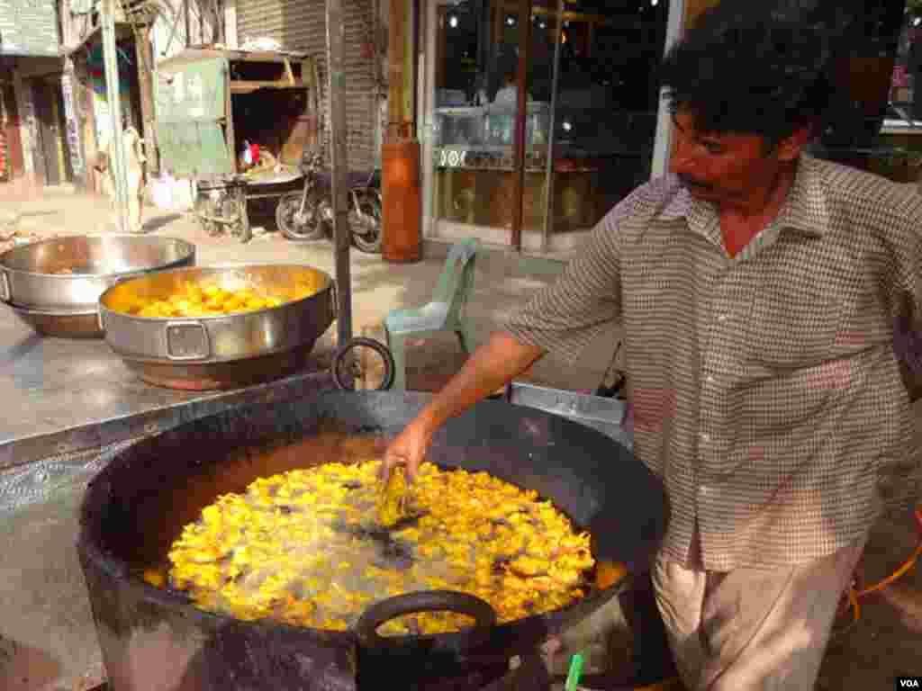 پکوڑوں کے بغیر رمضان کو نامکمل تصور کیا جاتا ہے۔ ایک دکاندار کڑاہی میں پکوڑے تل رہا ہے۔