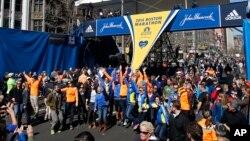 Участники Бостонского марафона с друзьми и родными фотографируются на финишной линии марафона за день до начала соревнований в воскресенье 20 апреля 2014 г.