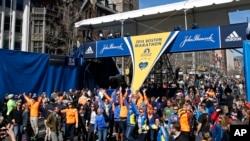 Các vận động viên, cùng với bạn bè và gia đình, chụp ảnh tại mức đến của cuộc đua marathon ở Boston, một ngày trước khi cuộc đua bắt đầu, 20/4/2014.