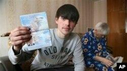 Remaja Rusia, Alexander Abnosov didampingi neneknya menunjukkan paspor Amerikanya kepada para wartawan di Cheboksary, Rusia (20/3).
