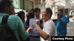 炎黄春秋杂志社负责人胡德华在被强占的办公地点外面接受外媒采访(网络图片)