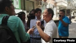 炎黄春秋杂志社负责人胡德华在被强占的办公地点外面接受外媒采访。(网友提供)