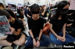 香港反送中示威者2019年8月12日在香港国际机场静坐示威时用黑布蒙眼,抗议警方一天前与示威者的冲突中使一名抗议者眼睛受伤。