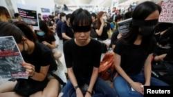 香港反送中示威者在香港国际机场静坐示威时用黑布蒙眼,抗议警方一天前与示威者的冲突中使一名抗议者眼睛受伤。(2019年8月12日)