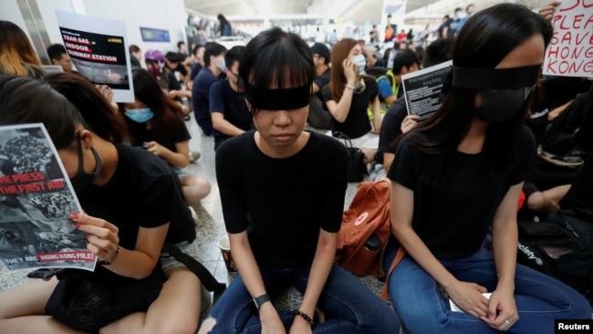 香港反送中示威者在香港國際機場靜坐示威時用黑布蒙眼,抗議警方一天前與示威者的衝突中使一名抗議者眼睛受傷。 (2019年8月12日)
