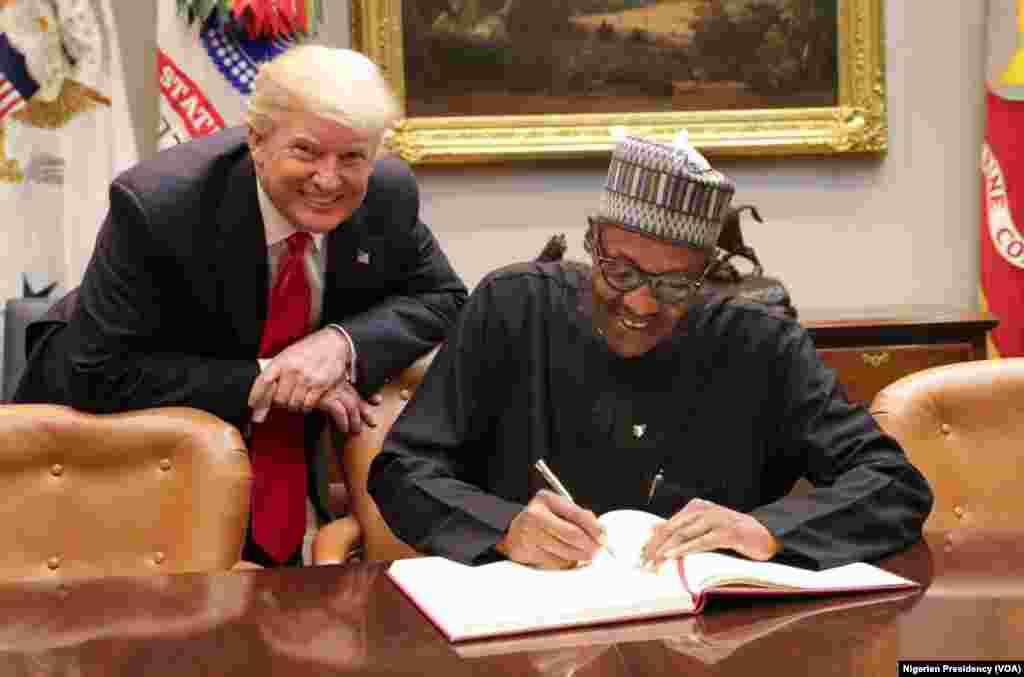 Shugaba Buhari a yayin da yake sa hannun kan wata takarda tare da Shugaba Trump.