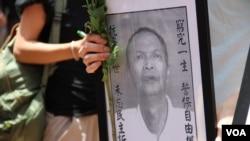 香港示威者手持李旺陽的遺照。