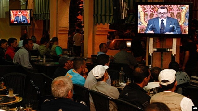 Moroccan customers at a cafe in Casablanca watch a live broadcast from Rabat of a speech by Morocco's King Mohammed VI, June 17, 2011