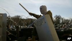 Maskirana osoba na barikadi ispred zgrade regionalne administracije u Donjecku