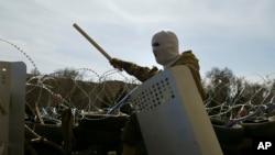 Một người đàn ông đeo mặt nạ đứng trên các chướng ngại vật tại tòa nhà chính quyền khu vực Donetsk, Ukraine, ngày 7/4/2014. Người biểu tình yêu cầu tổ chức trưng cầu dân ý như ở Crimea về việc tách khỏi Ukraine và trở thành một phần của Nga.