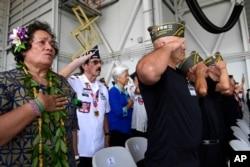 Personas que asistieron a una ceremonia por la llegada de los restos de se supone pertenecen a soldados que murieron en la Guerra de Corea, se ponen de pie durante el Himno Nacional en la Base Conjunta Pearl Harbor-Hickam, Hawai, el miércoles 1 de agosto de 2018.