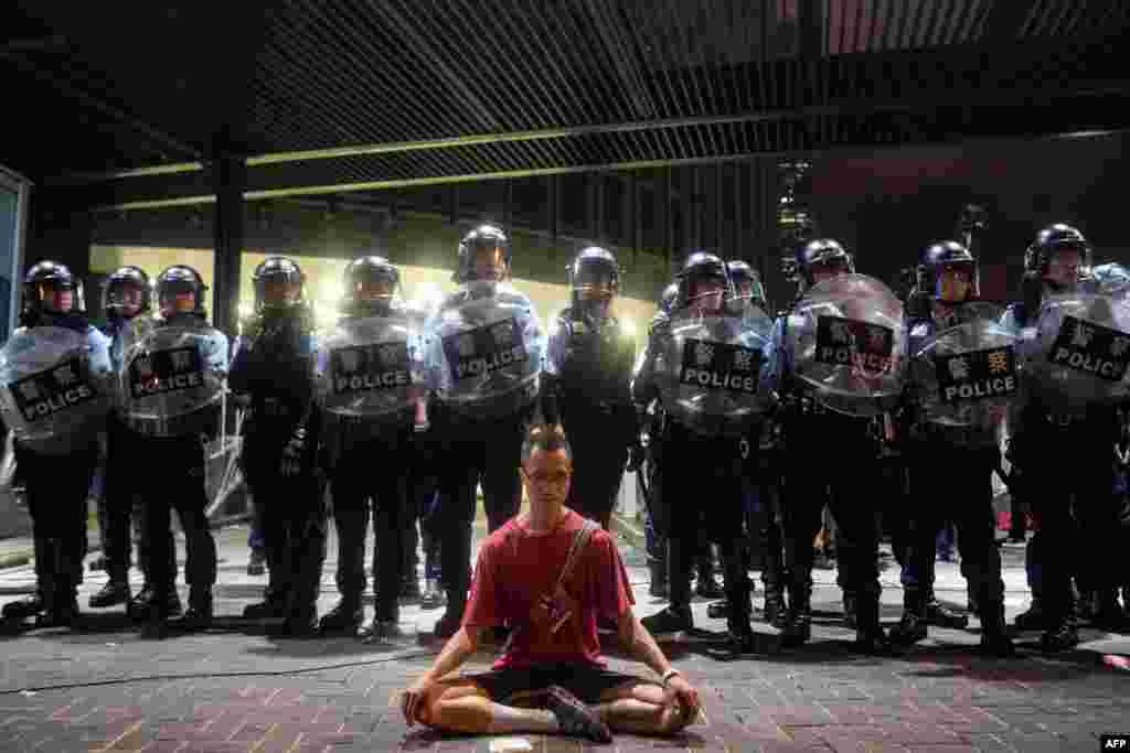 A protester meditates in front of police in Hong Kong, June 10, 2019. Hong Kong witnessed its largest street protest in at least 15 years as demonstrators protested a proposed law to allow extraditions to China.