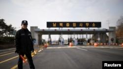 一名韓國保安在兩韓邊境通往朝鮮開城工業園區的道路旁執勤。(資料照片)