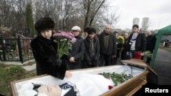 Bà Nataliya Magnitskaya mẹ của ông Sergei Magnitsky đứng cạnh quan tài của ông trước khi mai táng