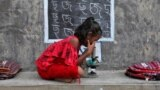 A girl, who does not have access to internet facilities and gadgets, uses a microscope as she attends an open-air class outside a house with its walls converted into black boards following the closure of their schools due to the coronavirus disease (COVID