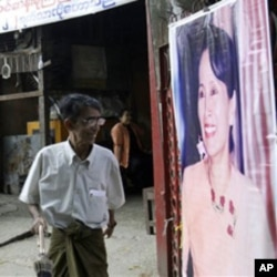 A member of Burna's detained opposition leader Aung San Suu Kyi's National League for Democracy party walks past her portrait outside the party's headquarters, Rangoon.