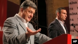 Ukrainian presidential candidate Petro Poroshenko, left, talks with Vitali Klitschko, at right, during a press conference, in Kyiv, Ukraine, May 26, 2014.