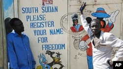 Southern Sudanese artists stand next to a painted sign in the southern capital of Juba urging people to register for the upcoming independence referendum, 30 Sep 2010