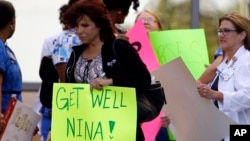 A Texas Health Presbyterian Hospital Dallas staff carries a sign wishing Nina Pham well, Oct. 16, 2014. (AP Photo/Tony Gutierrez)