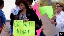 A Texas Health Presbyterian Hospital Dallas staff carries a sign wishing Nina Pham well as she and others wait for an ambulance carrying Pham to depart for Maryland, October16, 2014.