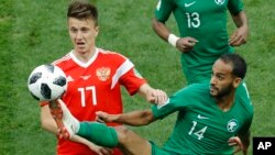 Russia's Roman Zobnin, left, and Saudi Arabia's Abdullah Otayf vie for the ball during the group A match between Russia and Saudi Arabia.