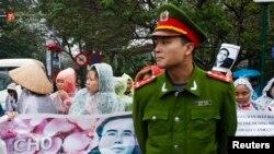 Seorang polisi berjaga di depan para pendukung pengacara Le Quoc Quan, yang berdemo di luar pengadilan di Hanoi (18/2).