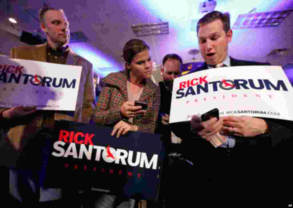 Supporters of Rick Santorum compare Iowa caucus returns at the Republican presidential candidate's victory party. (AP)