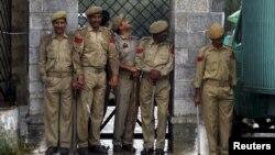 سری نگر میں پولیس اہل کار بارش سے بچنے کے لیے دیوار کی آڑ میں کھڑے ہیں۔ فائل فوٹو