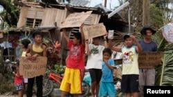菲律賓受到颱風海燕襲擊後﹐受影響地區兒童在公路旁高舉需要救援的標語牌。