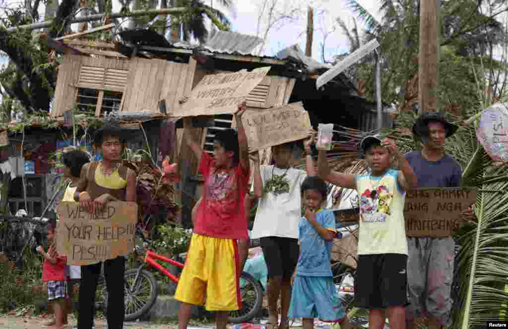 Anak-anak memegang papan bertuliskan permintaan bantuan dan makanan di pinggir jalan kota Tabogon, provinsi Cebu, yang dihantam topan Haiyan (11/11). (Reuters/Charlie Saceda)