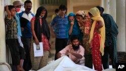 3일 방글라데시 건물 붕괴 사고 현장에서, 실종자 가족들이 사망자 시신을 확인하고 있다.