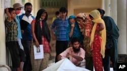Para anggota keluarga dan kerabat berusaha mengidentifikasi korban tewas akibat gedung runtuh di kota Savar, Bangladesh (3/5).