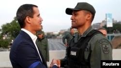 """Lãnh đạo phe đối lập Venezuela Juan Guaido, người được nhiều quốc gia công nhận là lãnh đạo lâm thời hợp pháp của đất nước, bắt tay với một giới chức quân sự gần căn cứ không quân Generalisimo Francisco de Miranda """"La Carlota"""", ở Venezuela, ngày 30/4/019."""