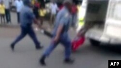A picture grabbed on an amateur video and released by the South African Daily Sun newspaper shows policemen holding the legs of a Mozambican taxi driver handcuffed to the back of a police van while being dragged by the van in Daveyton, Feb. 28, 20313.